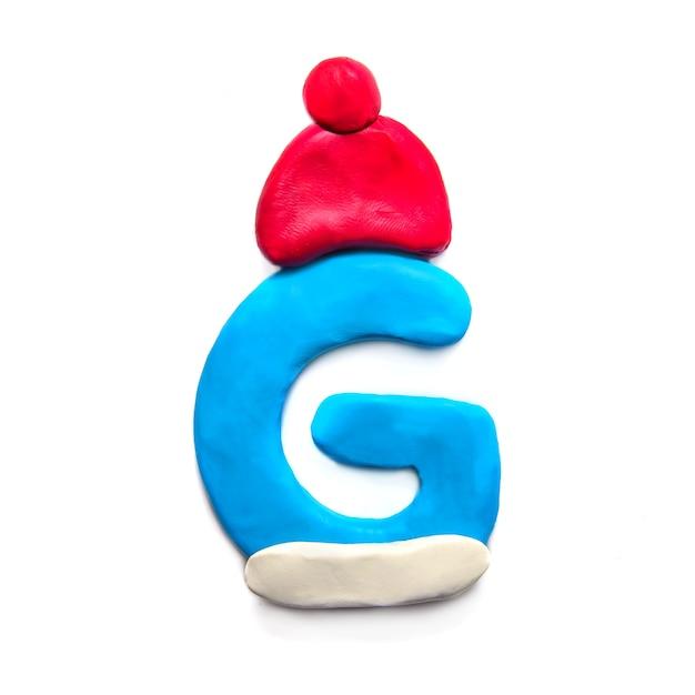 Синяя пластилиновая буква g алфавита в зимней красной шляпе на белом фоне Premium Фотографии