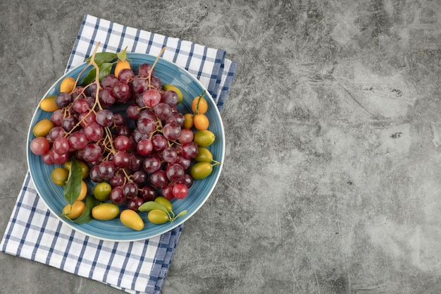 大理石の表面にキンカンフルーツと赤ブドウの青いプレート。 無料写真