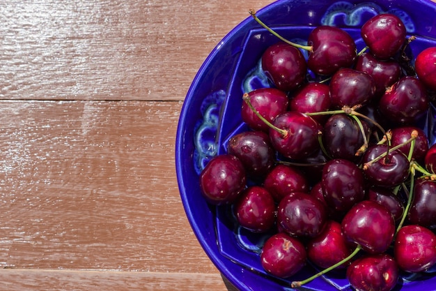 Blue plate of ripe sweet cherry on  wooden table Premium Photo