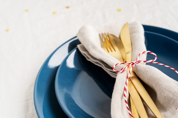 Blue plates and golden cutlery in a napkin Premium Photo