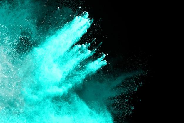 黒の背景に青い粉の爆発。フリーズモーション。 Premium写真