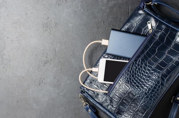 Blue power bank и телефон в женской сумке. темно-серый бетонный фон. копировать пространство Premium Фотографии