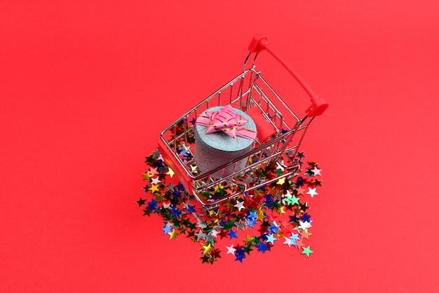 ショッピングカートにピンクの弓と赤い背景の紙吹雪と青いプレゼントボックス。 Premium写真