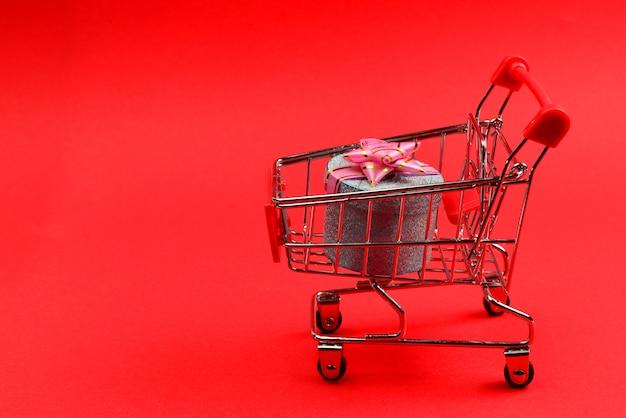 赤い背景のショッピングカートにピンクの弓と青いプレゼントボックス。 Premium写真