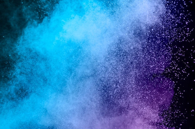 Blue and purple dust of powder on dark background Free Photo