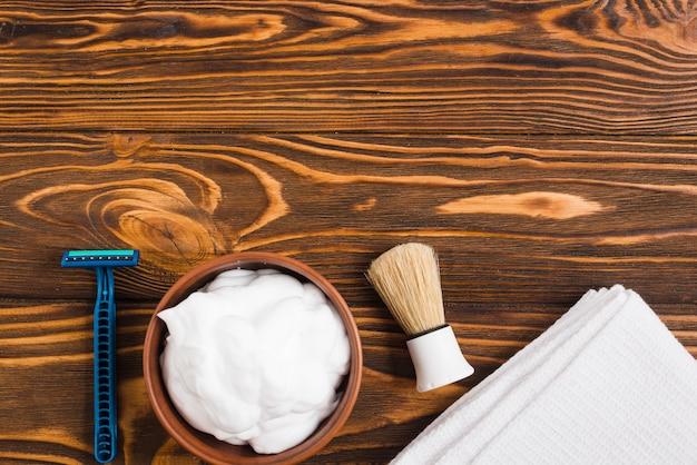 Blue razor; foam; shaving brush and white folded napkin against wooden surface Free Photo