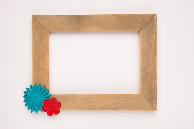Blue and red flower on the corner of wooden empty frame isolated on white backdrop Free Photo