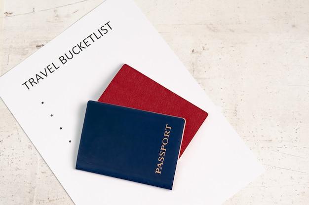 Blue and red travel passports, next to the inscription travel bucketlist Premium Photo