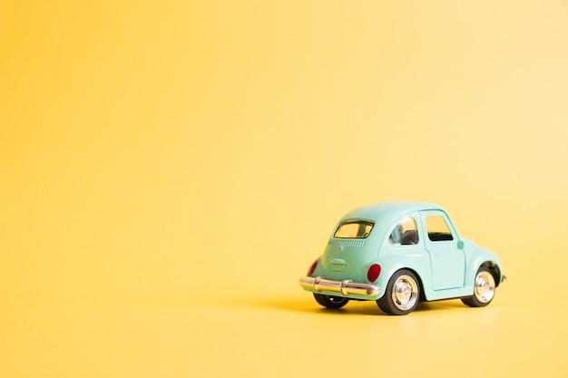 Blue retro toy car on yellow. summer travel concept. taxi Premium Photo