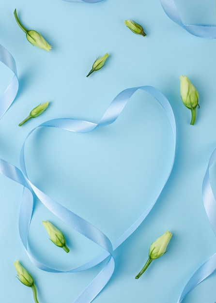 Blue ribbon in a heart shape with flower buds. Premium Photo