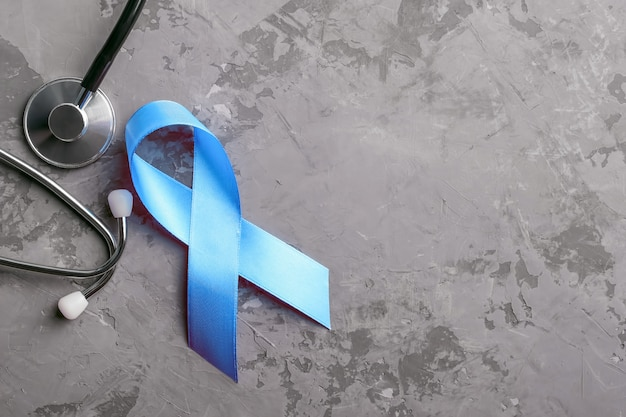 Blue ribbon and stethoscope on grey concrete background, prostate cancer awareness concept. Premium Photo