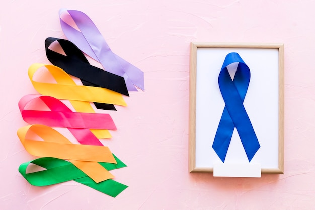Blue ribbon on white wooden frame near the row of colorful awareness ribbon Free Photo