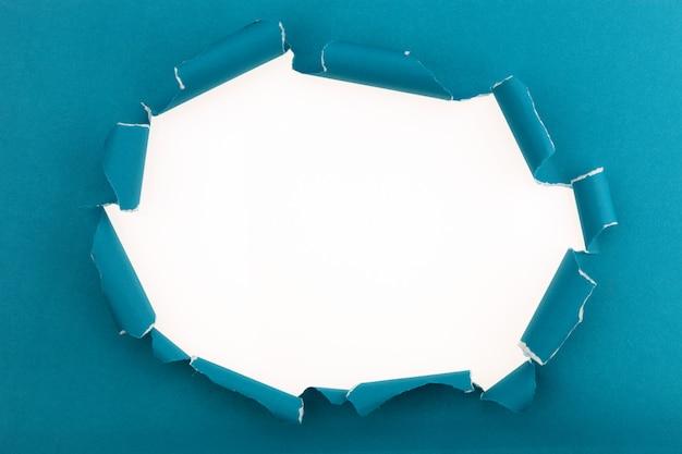 青は、白い背景に白い破れた紙にあなたのメッセージのためのスペースの開いた紙をリッピングしました。 Premium写真