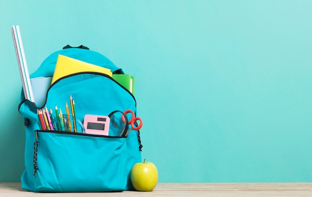 Blue school backpack with essential supplies Free Photo