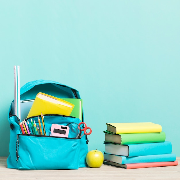 Blue school backpack with supplies and textbooks Free Photo