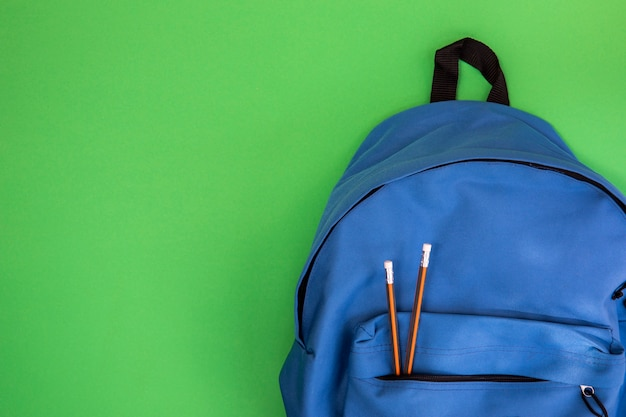 Blue school knapsack with pencils Free Photo