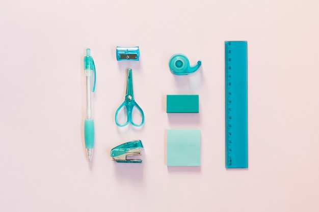 Blue school supplies on light pink surface Free Photo