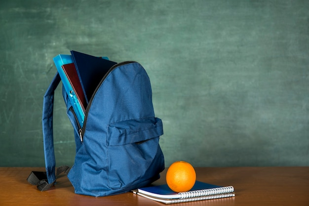 Blue schoolbag with copybook and orange Free Photo