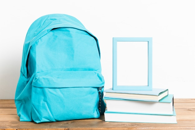 Blue schoolbag with empty frame on books on wooden table Premium Photo