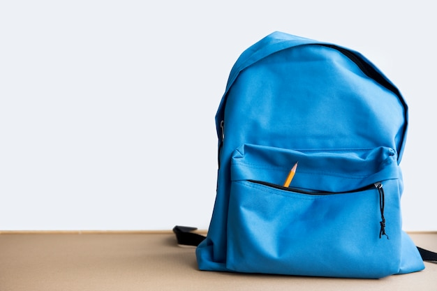 Blue schoolbag with pencil in pocket Free Photo