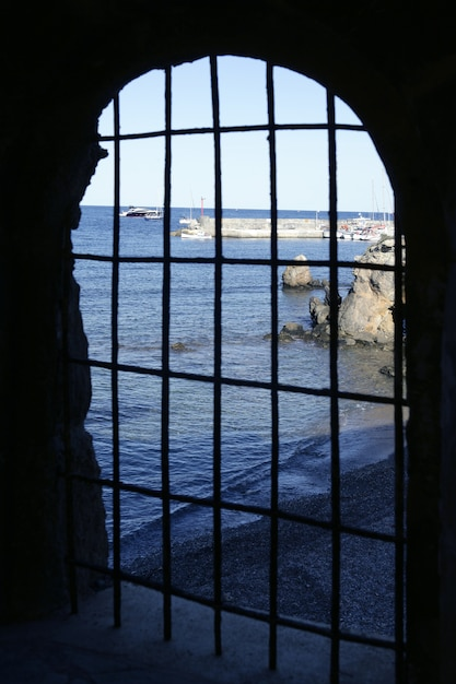 Blue sea behind the jail, arch window Premium Photo