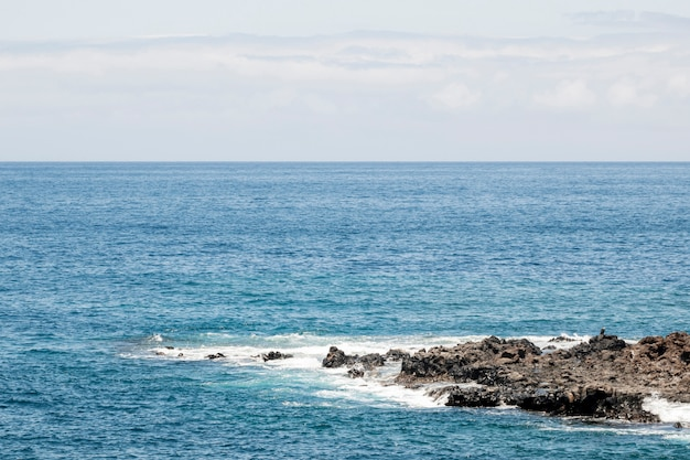 Blue sea with rocky littoral Free Photo