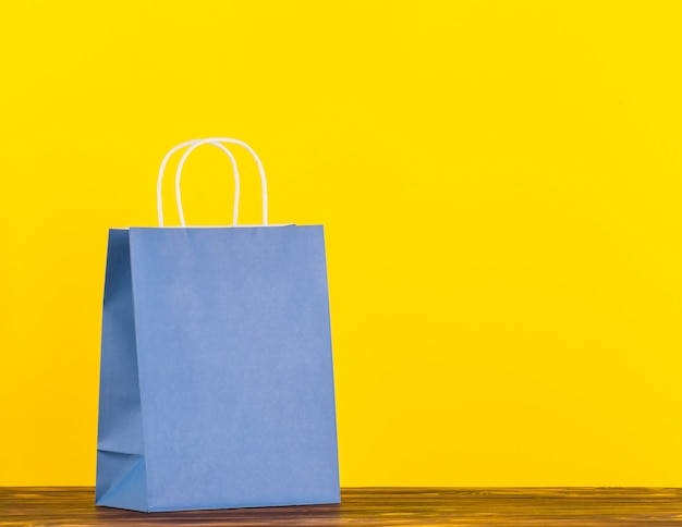 Blue single paper bag on wooden surface with yellow backdrop Free Photo