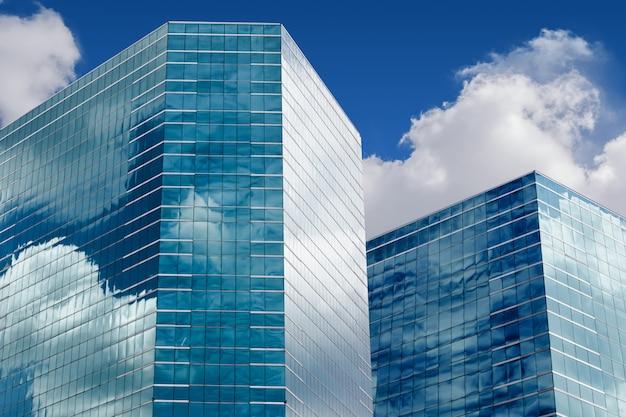 Голубое небо и облака, отражающие в окнах современного офисного здания Premium Фотографии