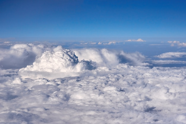 Blue sky above the clouds from airplane window Premium Photo