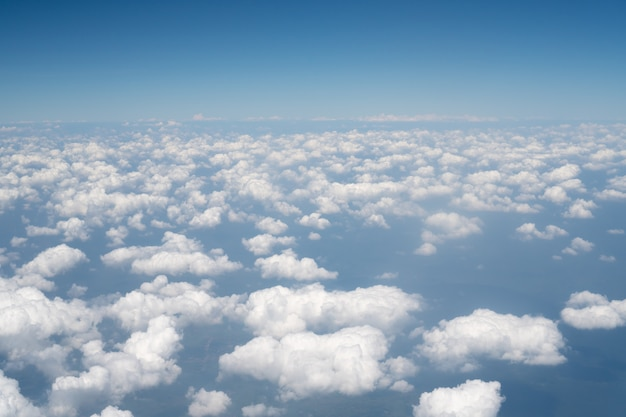 Blue sky view above the white mostly cloudy from the airplane window Premium Photo
