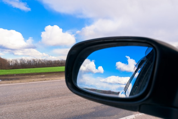 The blue sky with white clouds is reflected in the car mirror during the day Premium Photo