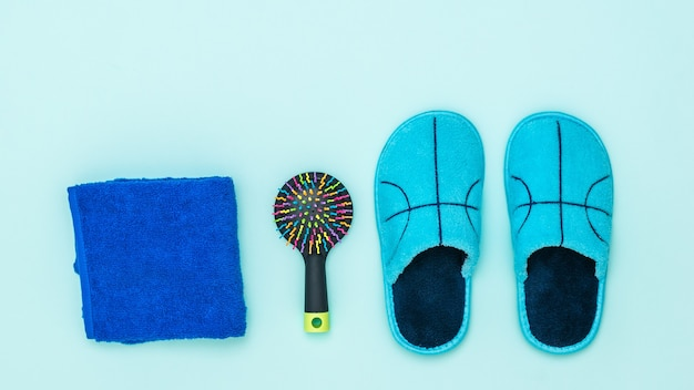 Blue slippers, towel and comb on blue background. set of morning accessories. Premium Photo