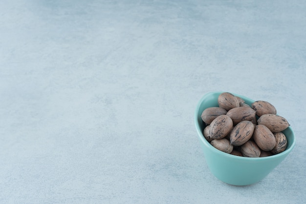 A blue small plate full of nuts on marble background. high quality photo Free Photo