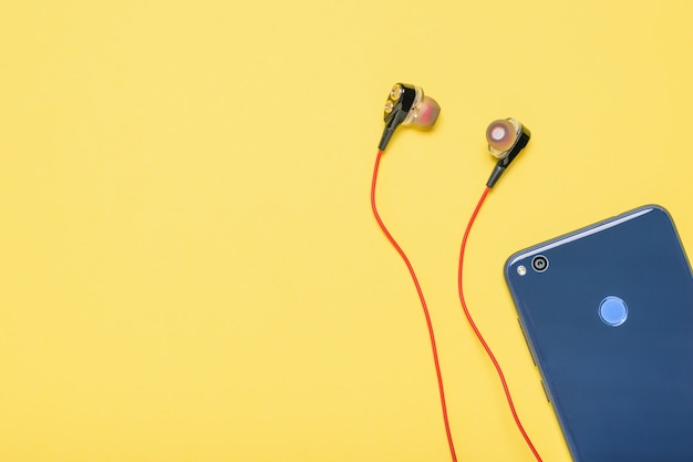 Blue smartphone with red headphones on yellow background. Premium Photo