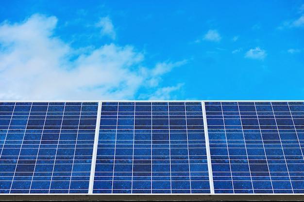 Blue solar panels (solar cell) with blue cloud sky background in solar farm. Premium Photo