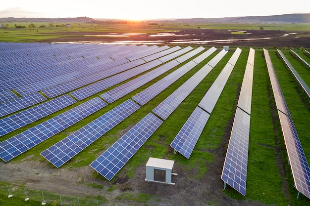 Blue solar photo voltaic panels system producing renewable clean energy on rural landscape and setting sun . Premium Photo