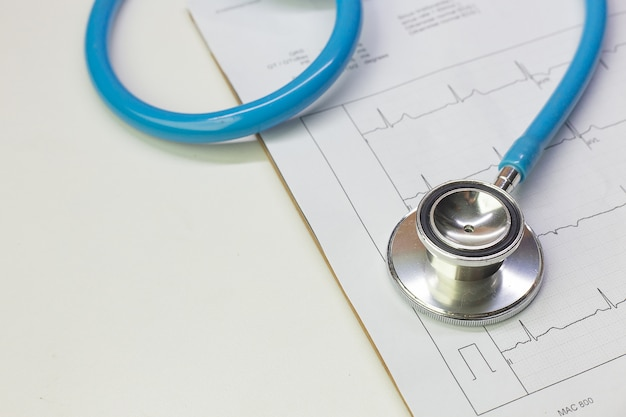 Blue stethoscopes and electrocardiography chart close up image. Premium Photo