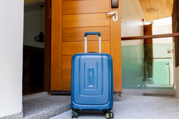 Blue suitcase in light hotel room with brown wooden details. copy space Premium Photo