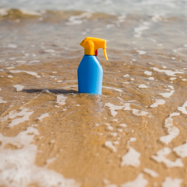 Blue sunscreen plastic bottle in the shallow sea water at beach Free Photo