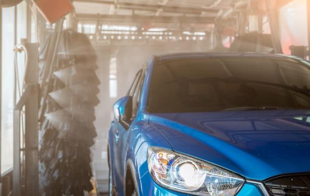Blue suv car washing by automatic car washing machine Premium Photo
