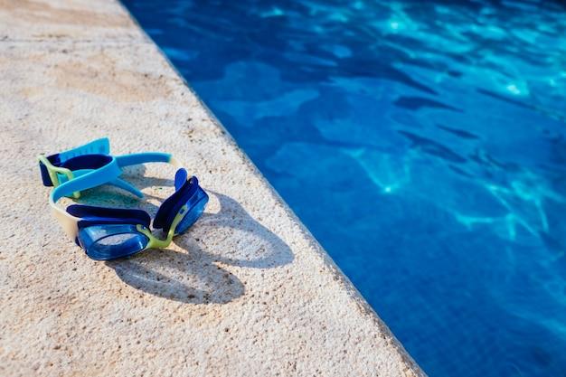 Синие очки бассейна, освещенные летним солнцем на краю частного бассейна. Premium Фотографии