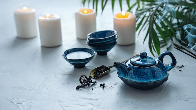 Blue tea set for chinese tea ceremony. burning candles and scented couples. Premium Photo