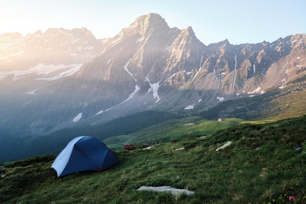 Blue tent on a grassy hill with mountains and clear sky Free Photo