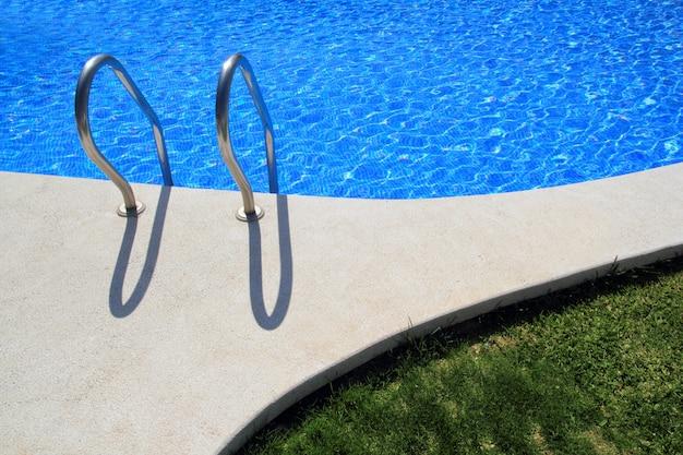 Blue tiles swimming pool with green grass garden Premium Photo