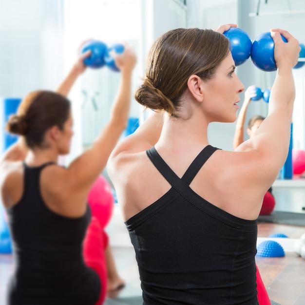 Blue toning ball in women pilates class rear view Premium Photo