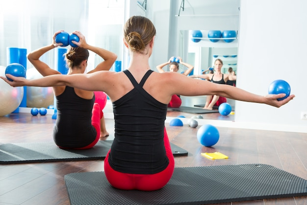 Blue toning ball in women pilates class rear view Premium Photo