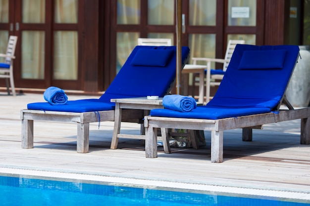 Blue towels on loungers near swimming pool at tropical resort Premium Photo