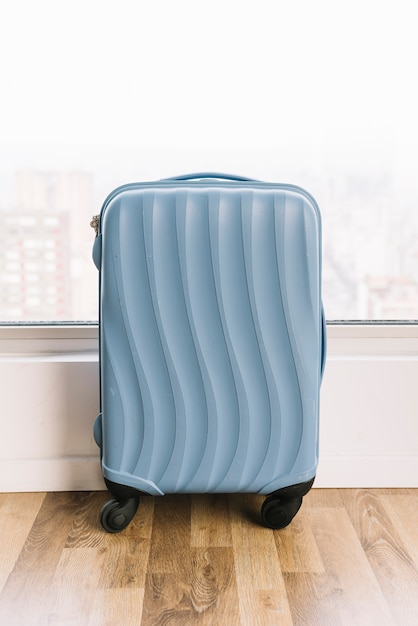 Blue travel suitcase near the window on wooden floor Free Photo
