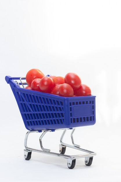 Blue trolley full of fresh tomatos Premium Photo