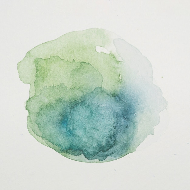 Blue and verdant paints in form of circle on white paper Free Photo